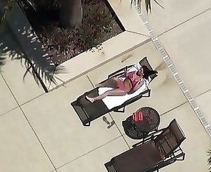 Pink bikini brunette sunbathing near a huge pool